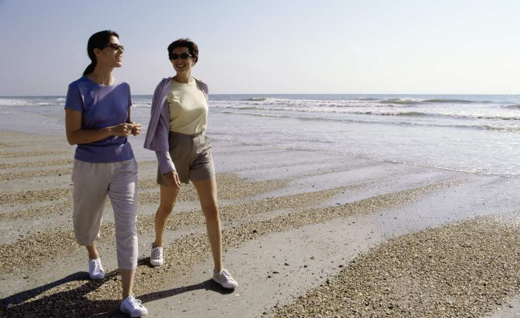 Two mid adult women walking on the beach