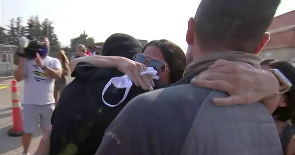 Lisa hugging her husband and sons after reuniting with them