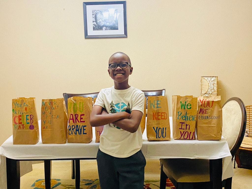 Orion Jean next to the meals he donated