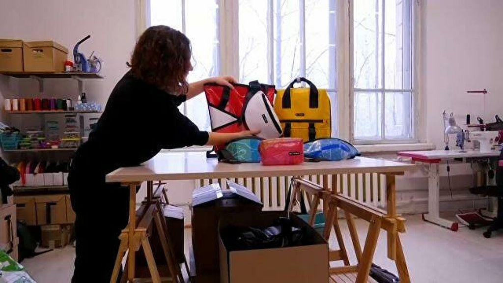 Woman arranging recycled bags on a table inside a workshop