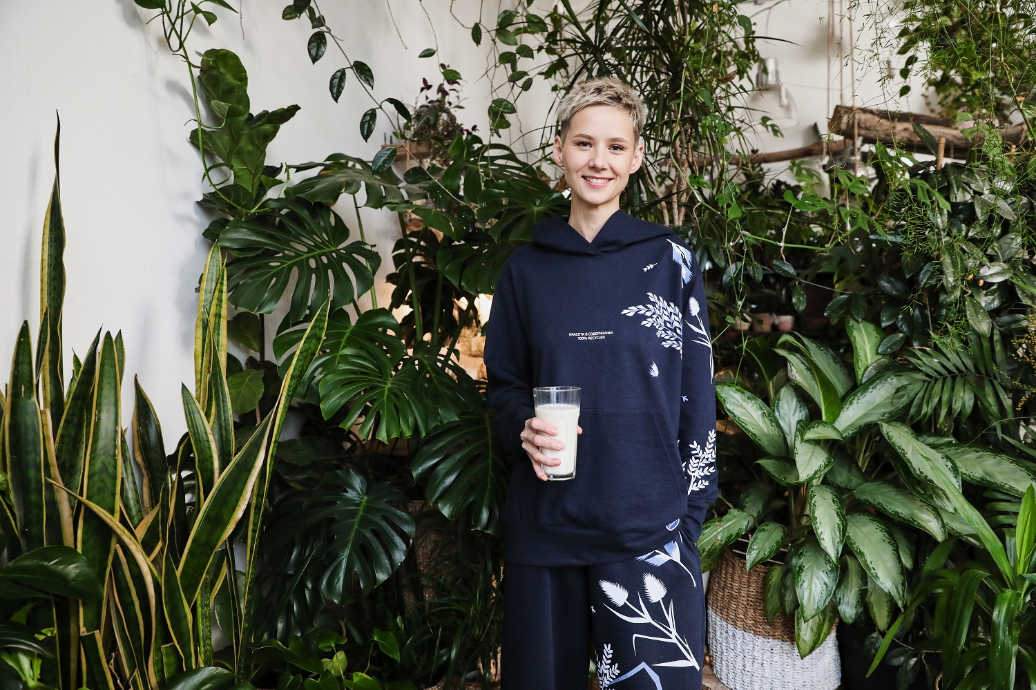 Olga Glagoleva, head designer at 99Recycle standing in front of green potted plants holding a glass of milk