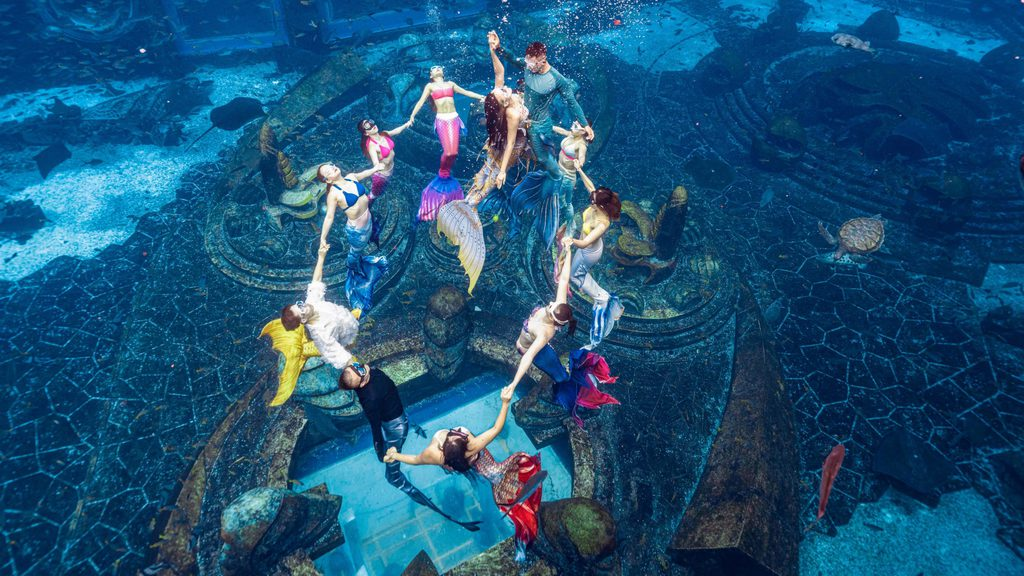 Women dressed as mermaid doing a formation in water